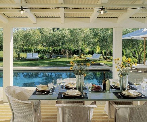 "For the covered porch off the poolhouse, the couple paired a zinc table of the architect's design with wicker chairs. The sloping lawn leads to a chicken coop Howard Backen crafted. ""It's lovely to sit in the shade on the chaise longues, under the row of olive trees,"" notes Lori Backen."