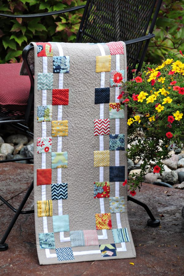 Modern table runner made using a charm pack.