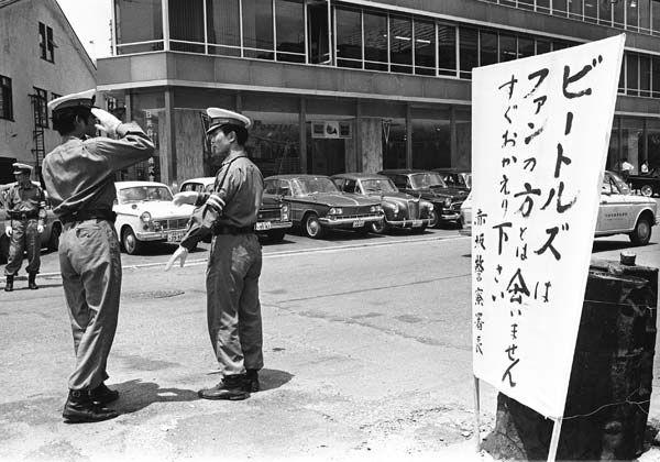 昭和41年、メンバーが宿泊するホテルの近くに張り出された、ファンにホテルに近づかないよう注意を促す看板と警備の警官。英人気ロックバンド、ザ・ビートルズが初来日、6月30日から7月2日まで武道館で公演した(東京都) (1966年06月撮影) 【PANA=時事】
