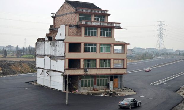 A house sits awkwardly in the middle of a newly built road in Wenling, Zhejiang province in China. An elderly couple refused to sign an agreement to allow their house to be demolished. They say that compensation offered is not enough to cover rebuilding costs. Photograph: China Daily/Reuters