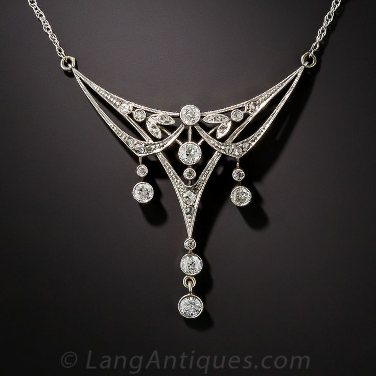 Edwardian Diamond Necklace. Artfully and delicately hand crafted in platinum over 15K gold (hence more than likely of British origin), this quintessential Edwardian jewel displays a curvaceous feminine design that perfectly defines the period. Three diamond dangles dance below stylized diamond-set garlands reminiscent of the classic Art Nouveau whiplash motif from around the same period (circa 1910). Exquisite is the word. 1 1/2 by 1 1/4 inch. The newer white gold chain measures 17 inches.
