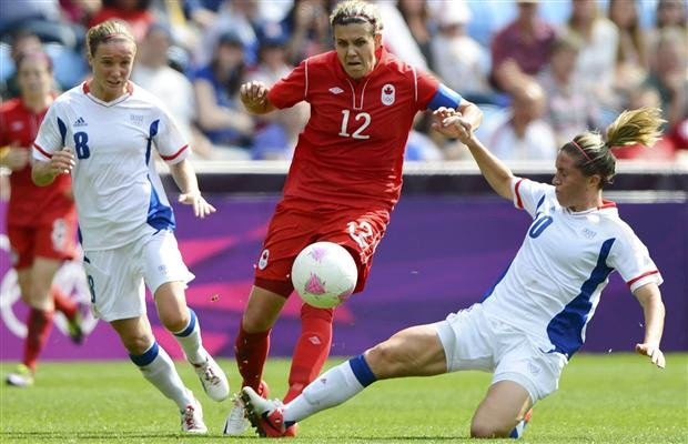 Canada's Christine Sinclair is challenged by France's Sonia Bompastor (L) and Camille Abily (R) in the women's bronze medal soccer match in Coventry at City of Coventry Stadium at the London 2012 Olympic Games August 9, 2012.