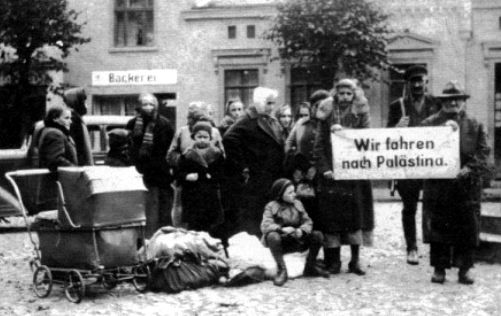 """German paramilitary occupants (members of Volksdeutscher Selbstschutz) in Sępólno Krajeńskie, Poland gathered Jews at the city's marketplace in the autumn of 1939. The German sign they are holding reads, """"We are going tomore..."""