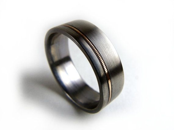 Titanium with guitar string inlay. This would be the perfect ring for Seth!