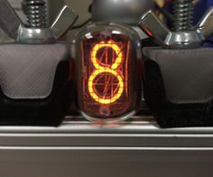 A Nixie Tube is a Neon gas-filled tube, that has a wiremesh anode with various cathodes shaped like numbers or symbols.  Back in the 1950s they were u...