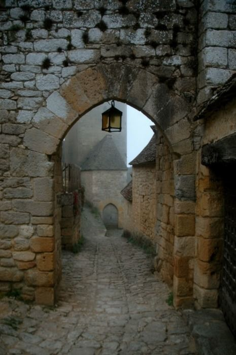 Medieval village Dordogne, France. Stone archways hang over the cobblestone road into many towns in southwest France.