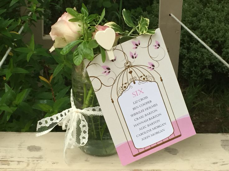 Close up of vintage birdcage table plan card in country floral jar for vintage table plan Fuschia.