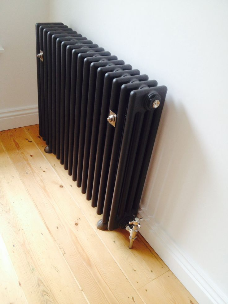 Acova steel grey column radiator with cast iron feet, modified wall brackets and tap style valves