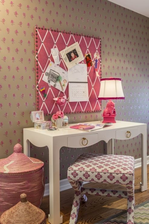 Beautiful girl's room features pink and gray wallpaper as a backdrop for a hot pink, ribbon trimmed, pin board over Bungalow 5 Jacqui Desk topped with hot pink foo dog lamp paired with x-based stool situated next to pink Senegalese baskets.