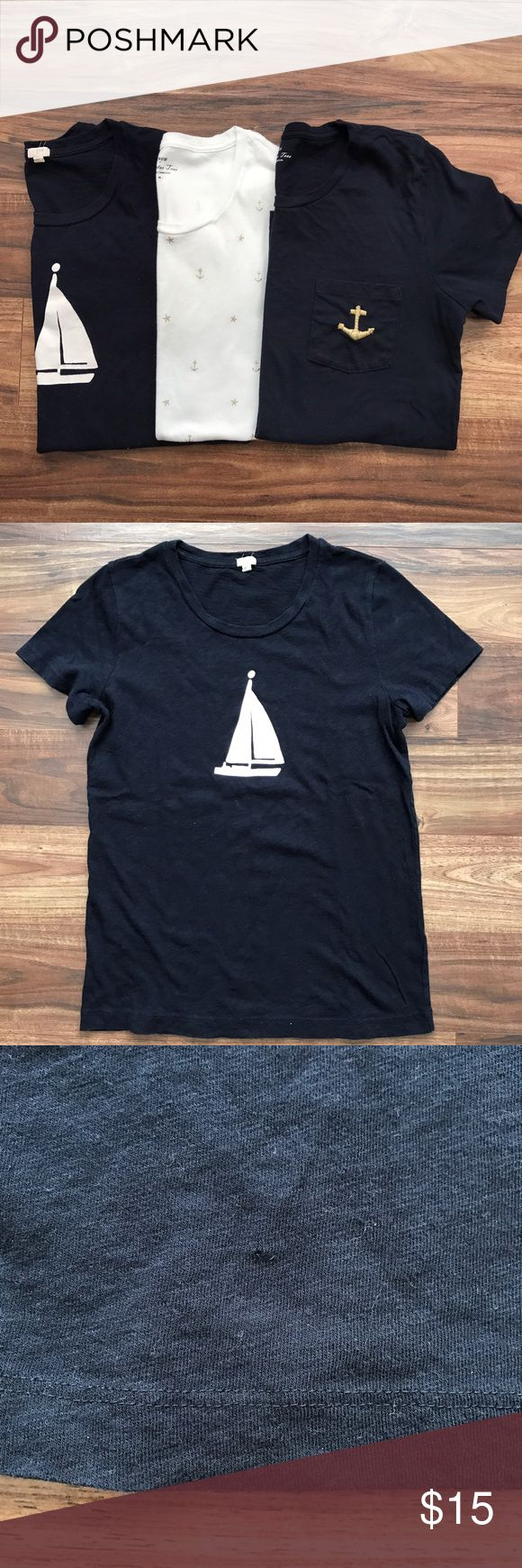 J Crew Nautical Tee Shirts Set of 3 well loved J Crew Nautical themed tee shirts.  The first is solid navy with a white sailboat.  There is a very small hole on the bottom near the hem and some pilling, shown in the pictures.  The second is ivory with gold foil anchors and stars.  There is a small pull near a star on the chest and some pilling, shown in the pictures.  The last is a darker solid navy with an embroidered gold anchor on a chest pocket.  Again, well loved but still cute to throw…