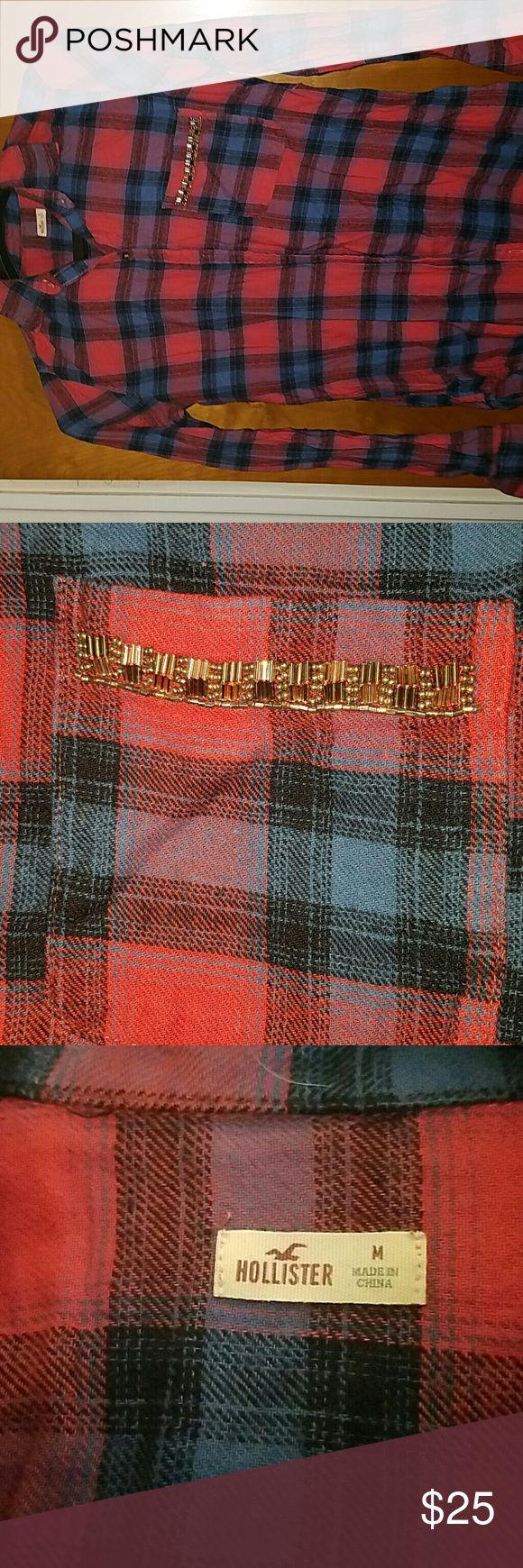 NWOT Hollister flannel shirt Size M Never worn button down flannel shirt from Hollister. Pink and blue flannel. Embellishment on pocket Hollister Tops Button Down Shirts