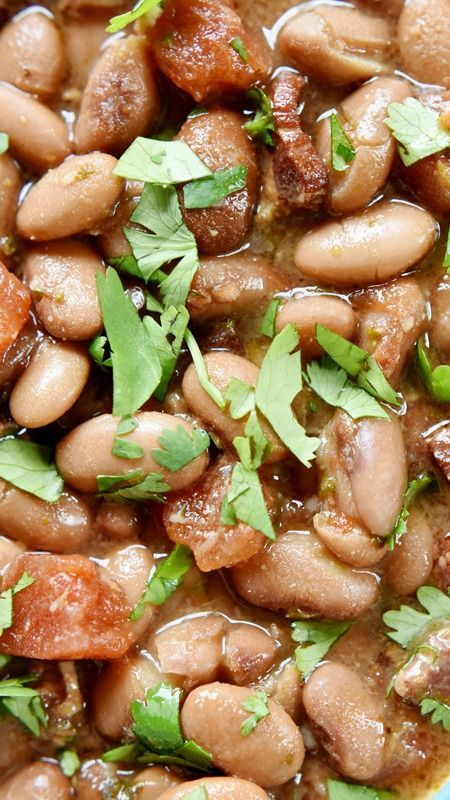 Slow Cooker Charro Beans ~ flavored with bacon, garlic, tomatoes, green chiles, jalapeños, cilantro, and spices -- are the perfect pinto beans to accompany your favorite Mexican entrees!