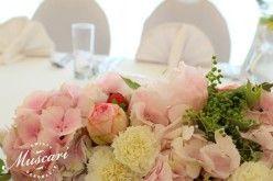 hortensje, róże, piwonie, goździki i zieleń w kompozycji na stole pary młodej