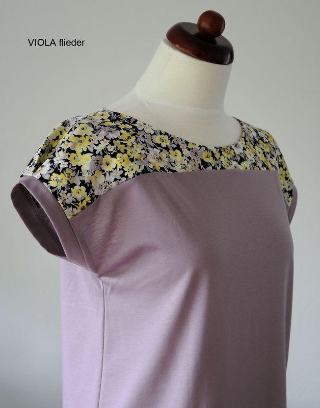 VIOLA ist ein oversized T-Shirt aus fliederfarbenem Jersey mit einer Passe aus Baumwollsatin mit Blumen-Print. Die überschnittenen Schultern werden am Ärmelsaum mit einer kleinen Falte in Form...