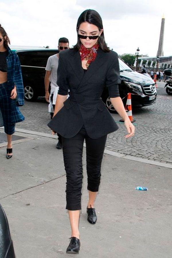 Kendall Jenner apostou em terno acinturado preto arrematado com óculos vintage e lenço vermelho.