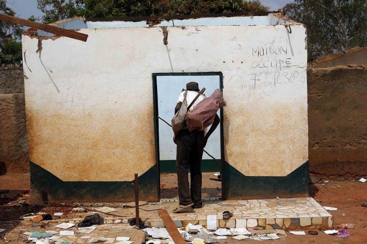 Een christen zoekt naar goederen tussen de resten van een huis in Bangui.