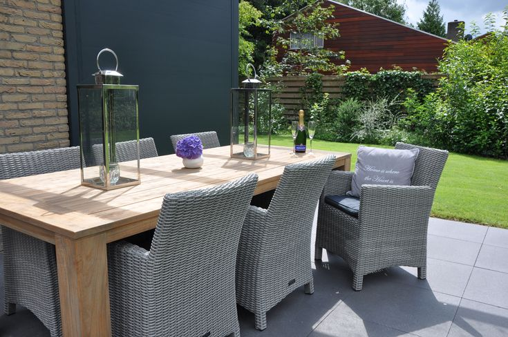 Teakhouten tafel gecombineerd met grijze gevlochten stoelen