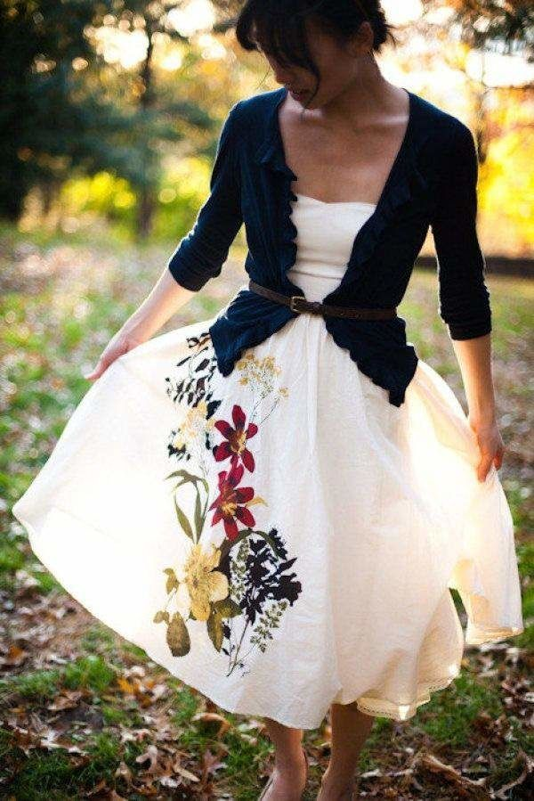 A floral illustrated wedding dress with a navy cardigan and belt.