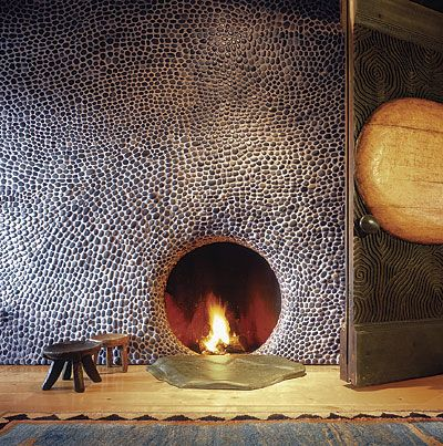 A wall-size mosaic of small, smooth river rock surrounds a round fireplace.