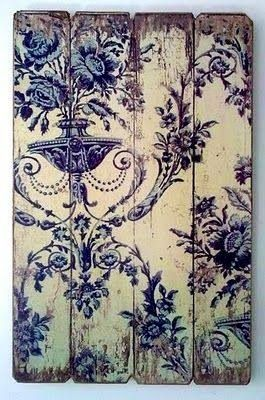 A scrap of traditional wallpaper is adhered to pallet wood, then distressed and antiqued for a wall art piece