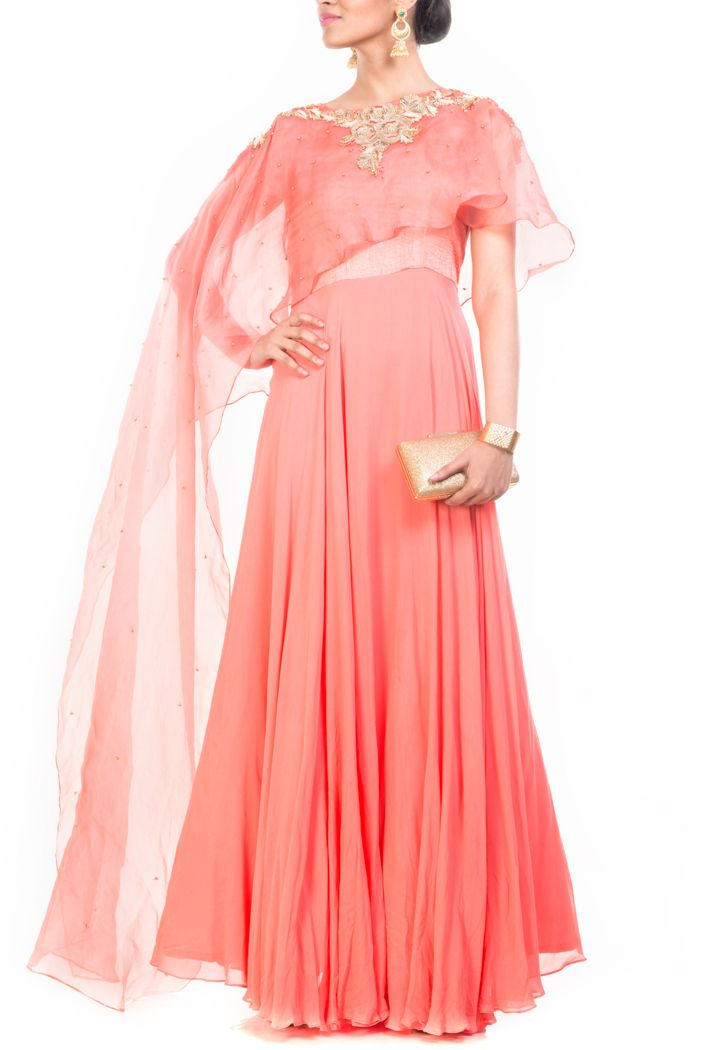 Featuring a light salmon gorgette gown with attached long organza cape. The neckline of the cape is embelished with zardozi work by using mukesh, dabka pearl thread. The cape has been highlighted by golden pearl.