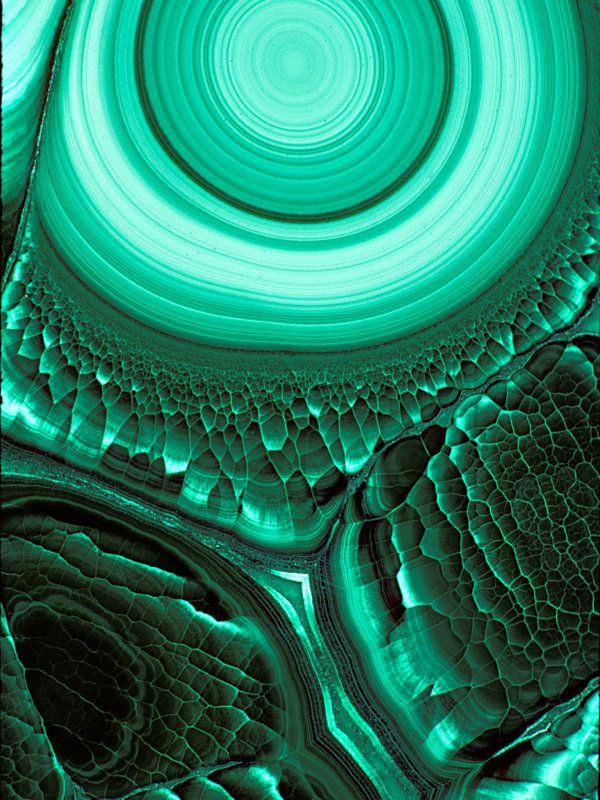 Malachite grows in layers of tiny crystals. Its colors correlate with different crystal sizes: small crystals form light green bands and larger crystals make darker ones.