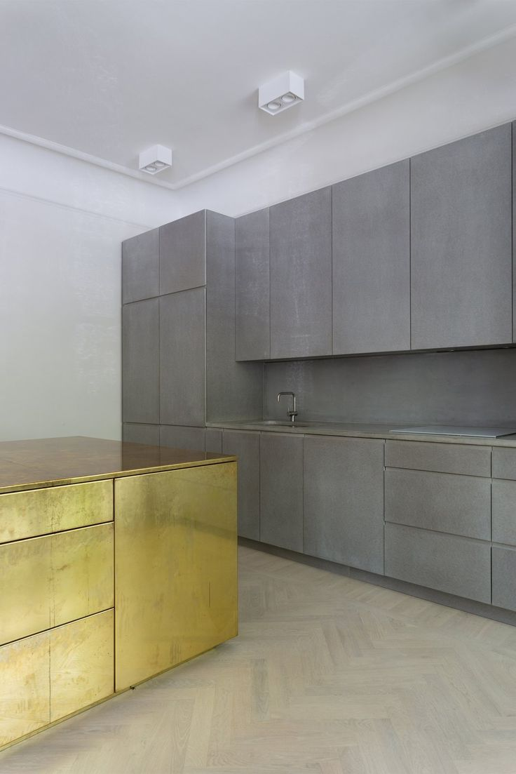 Kitchen in gray Valchromat, concrete and brass. Gold & Gray Apartment by Richard Lindvall.
