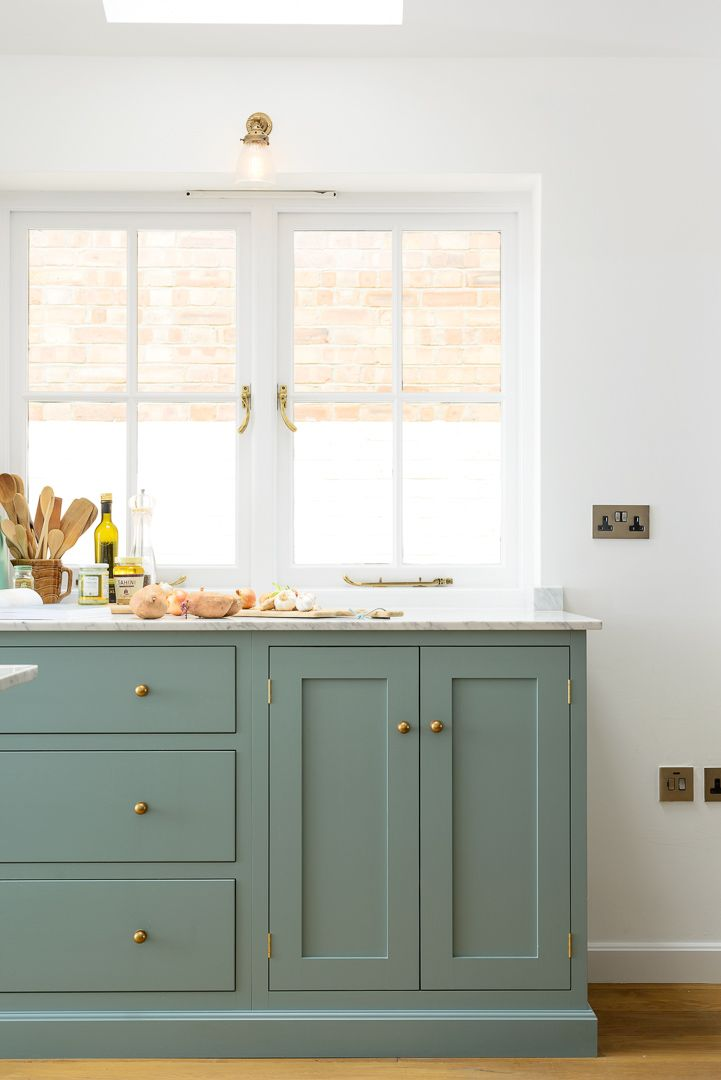 Lovely 'Trinity Blue' Shaker cabinets with Bella Brass knobs and smooth Carrara marble worktops