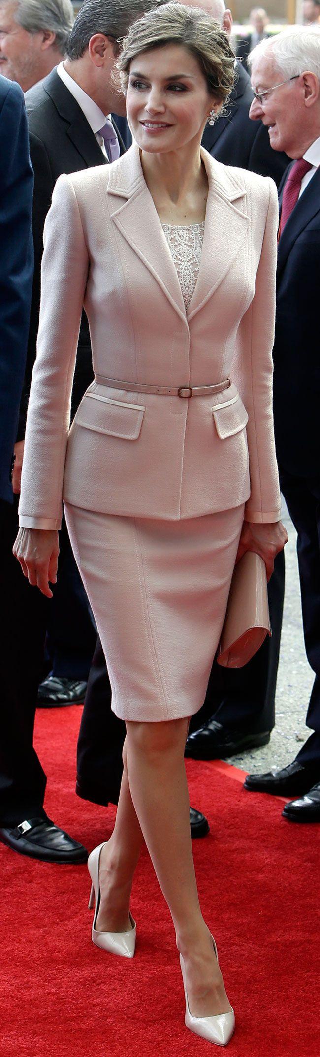 Doña Letizia ha repetido  un traje de chaqueta de Felipe Varela. Una pieza en color rosa empolvado, entallada y favorecedora para su figura, con esta ya lo ha lucido en cuatro ocasiones. Lo estrenó en noviembre de 2013 en EEUU, y la última en abril de 2015 para un acto en El Pardo con la Reina Sofía. Los zapatos de Prada en nude y la cartera de charol de Felipe Varela. Lo pendientes de diamantes son un regalo de los Reyes Juan Carlos y Sofía, antes de su boda con el Príncipe Felipe.