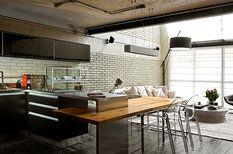 Černé skříňky v kuchyni jsou od značky Florense, deska jídelního stolu je z masivní borovice a na zakázku ji vyrobilo brazilské truhlářství Inovart