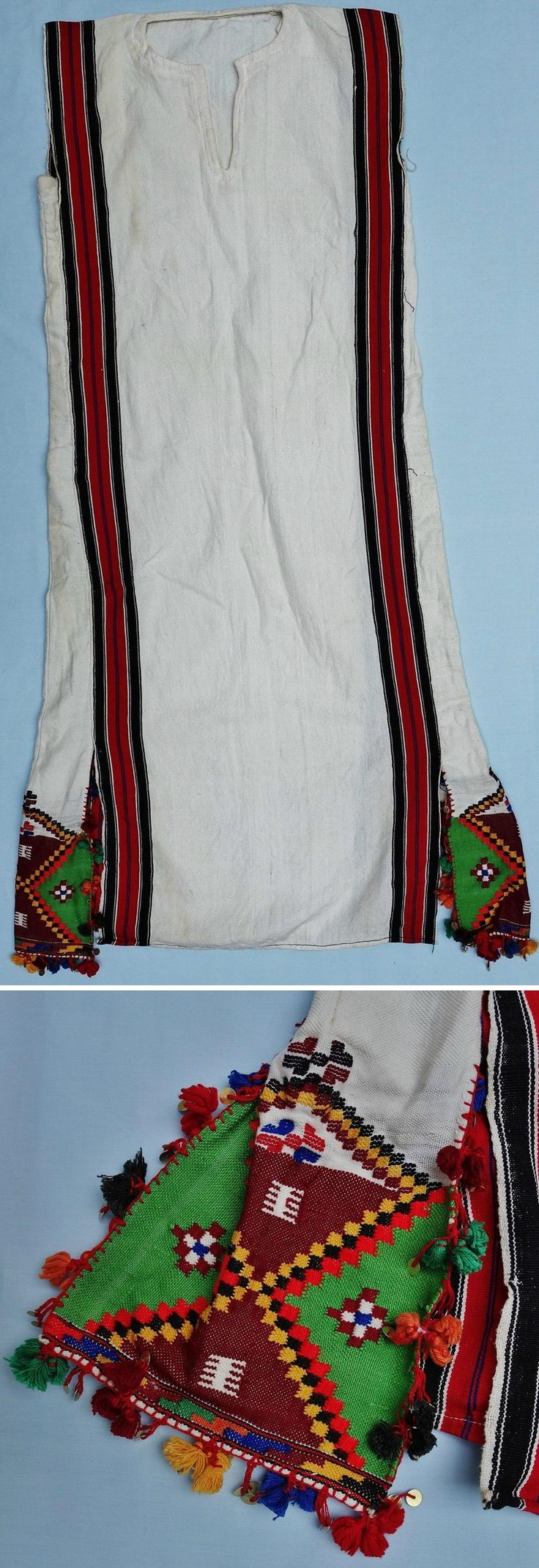 Cotton robe, from the Rhodopi mountains (around the town of Chepelare, Smolyan region) in southern Bulgaria.  Pomak, ca. 1980. Rural woman's dress with selvedge bands in black, white and red, and two woven blocks of decoration based on triangles and squares in dark red, green, yellow, black & mid-red. Around three edges of these woven blocks is an applied band of multi-coloured tassels with metal sequins.  The sleeves are missing.  (Textile Research Center, Leiden).