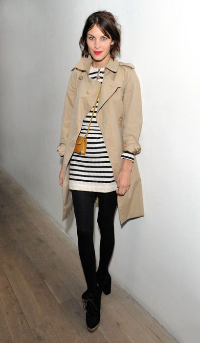 A khaki trench coat and simple striped dress with leggings.