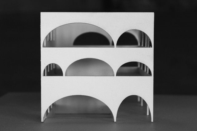 With obvious inspiration from Toyo Ito's Tama Art University Library in Tokyo. The arches help create a seemingly fragile structure protected by and in contrast to the heavy walls of the ruin.