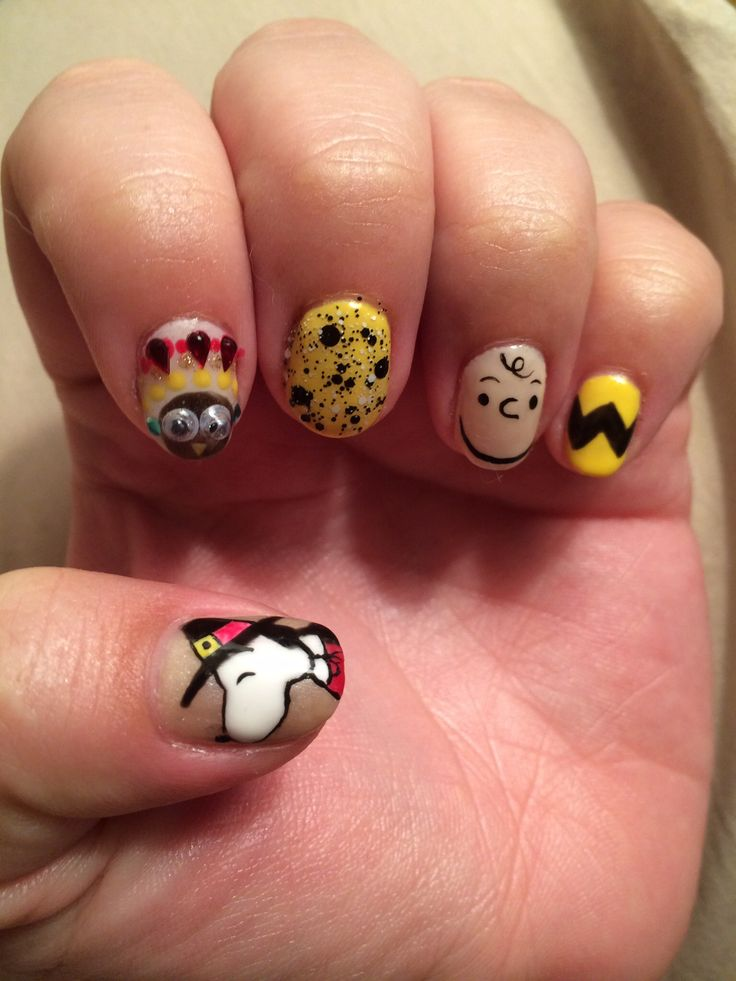 Peanuts Thanksgiving nail art inspired by A Charlie Brown Thanksgiving.  Thumb: Pilgrim Snoopy.  Index: Googly-eyed Indian Turkey.  Middle-Pinky: Charlie Brown inspired.  Nails by Angie Reyes at Two Brown Eyed Girls.