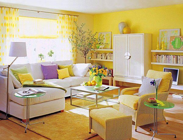 La base decorativa de este salón la ponen dos #colores cítricos: el #amarillo y el #verde lima, cuya viva presencia en las paredes y el suelo se compensa con mobiliario y #sofás blancos.