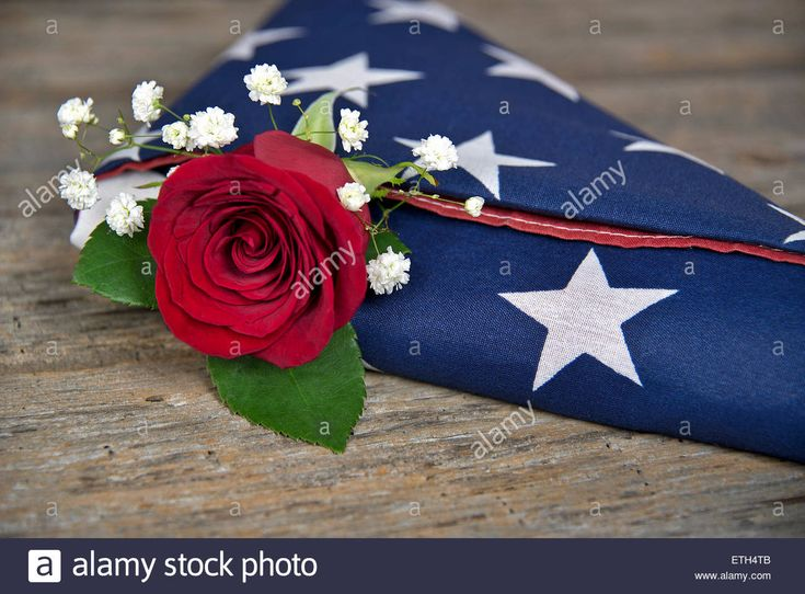 Download this stock image: Red rose in a folded American flag on rustic wood. - ETH4TB from Alamy's library of millions of high resolution stock photos, illustrations and vectors.