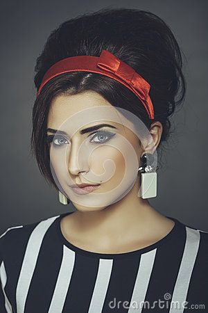 Portrait of an elegant enticing fashion female model wearing retro black-and-white stripped blouse, red headband and updo hairstyle, looking at the camera against dark background.