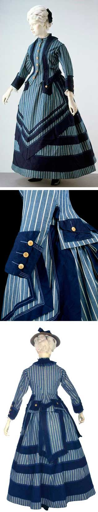 """Dress, U.K., ca. 1872. Cotton, trimmed with silk braid; bone buttons. Unlined. Victoria & Albert Museum: """"This is a jaunty, sensible woman's outfit of the early 1870s ... A hemline just at the ankle indicates a garment intended for walking outdoors. ... It is made of cotton, so it is easily washed and dried. Despite its practical use, the ensemble still incorporates the details of fashionable dress, with an overskirt in front and a bustle worn underneath at the back."""""""