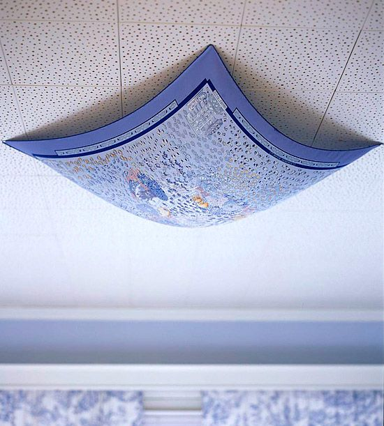 Tack a scarf or square of neat fabric to the ceiling over the light fixture. The fabric hangs far enough down that it won't heat up or scorch, and the pretty colored light shines through below