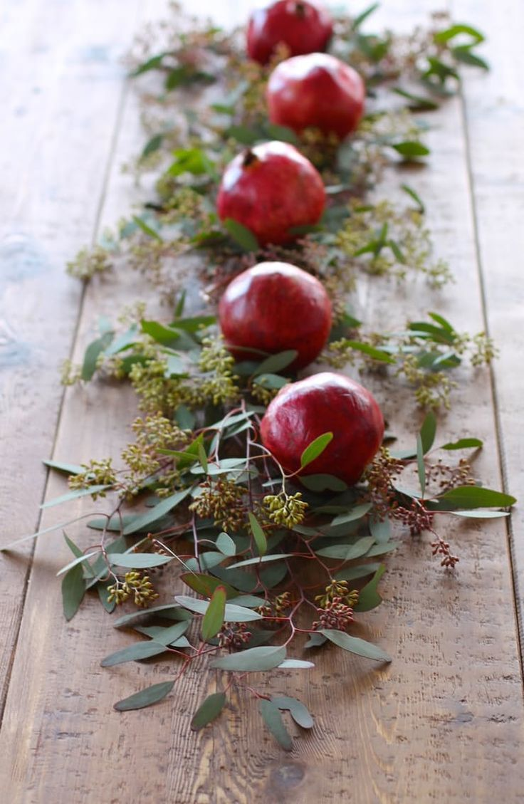 How To Decorate for Christmas With Only a Trip to the Grocery Store: Never underestimate the power of pomegranates. With their festive crimson shade and ornament-like shape, try pairing them with fresh greenery for a non-traditional table runner rendered in a traditional Christmas palette the way Julie Blanner did.