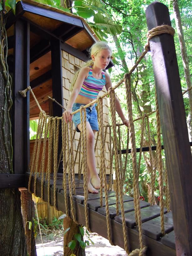 Wooden stairs and a rope bridge lead to this adorable playhouse. Cedar shingles help keep bugs away.