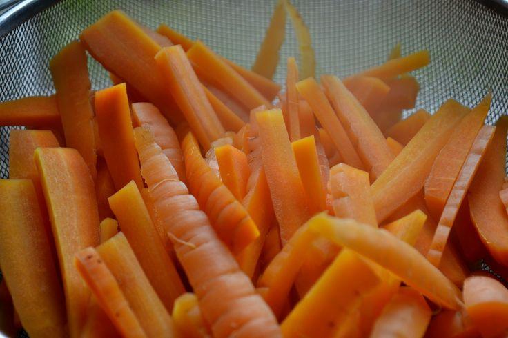 Goda frysta morötter Nykokta morotsstavar i en kökssil.