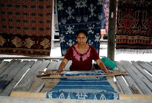 Sumba Lady of Rende, weaving a typical Rende Ikat weaving in natural dyes of blue indigo and other roots and bark of the trees for other colors.Sumba Ikat Weaving - Komodo, Indonesia