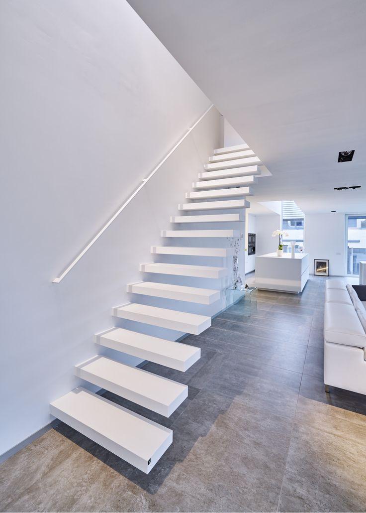 Moderne zwevende trap met Corian treden van Genico. Type Wallclimber Pure White van het Belgische merk Genico.