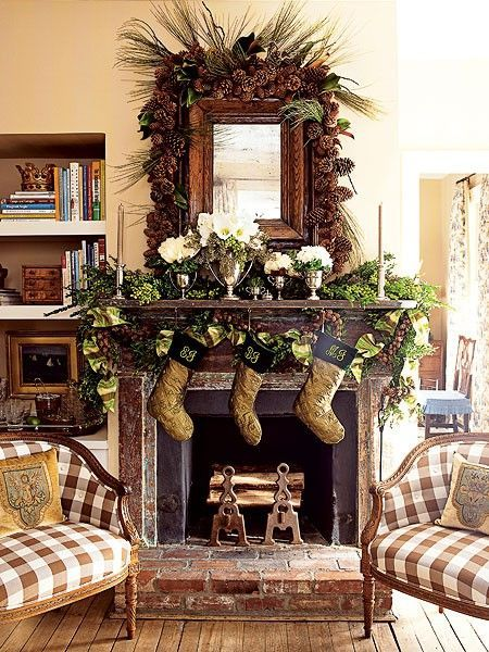 A pair of 10th-century Danish chairs flank the living room's fireplace & mantel, which is decorated w/ sprays of boxwood, plenty of pine cones, & flowers in all-white to match the brown-and-green Christmas stockings. The effect is charming & casual..