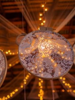 Not sure what these are called, but look like lace stretched on a large, round wooden embroidery frame and hung from barn rafters.