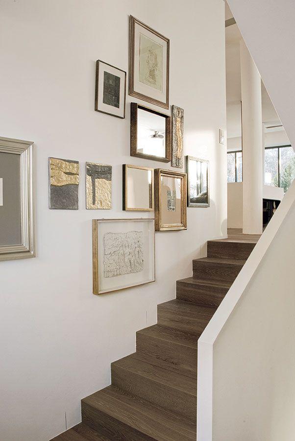 Schodiště má bílé zděné zábradlí ana jeho stěnách visí spousta uměleckých děl, artefaktů aúlovků zcest ve formě starých grafických listů aplastik. Lehce nazlátlý tón dubové podlahy se opakuje nejen na zdech vreliéfech Olbrama Zoubka, ale ivdetailech použitých na doplňcích, zahradním nábytku, svícnech na jídelním stole adalších předmětech. Foto Tomáš Vrána