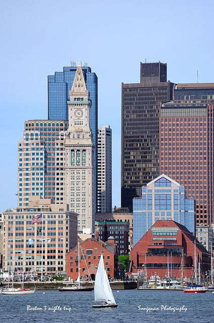 Boston, Massachusetts downtown urban architecture with boat and city skyline.