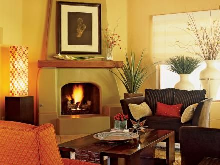 Aside from the fire, the rich color tones and soft furnishings bring warmth to this Southwestern-style living room. Container plants and bold accessories surround the soft green adobe fireplace and breathe life into the space. Design by Amy Bubier