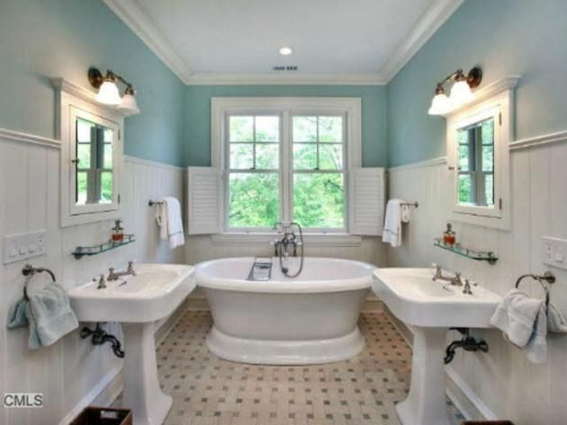 Symmetrical Bathroom With Pedestal Sinks And Free Standing Tub.